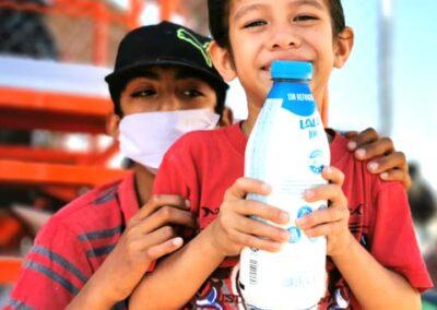 Niño sonriendo cargando bote de leche